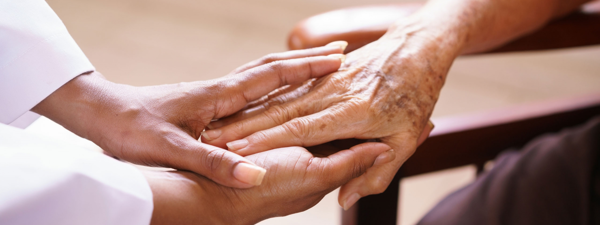 Caregiver and senior holding hands.